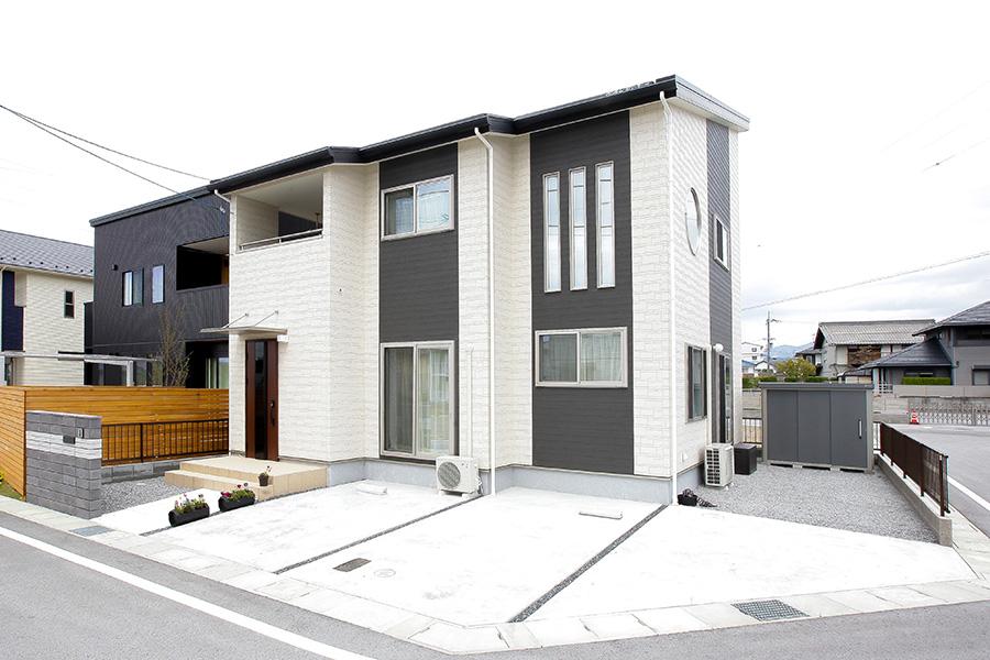 吹き抜けの上部に配置された丸窓が印象的な家の外観と駐車場